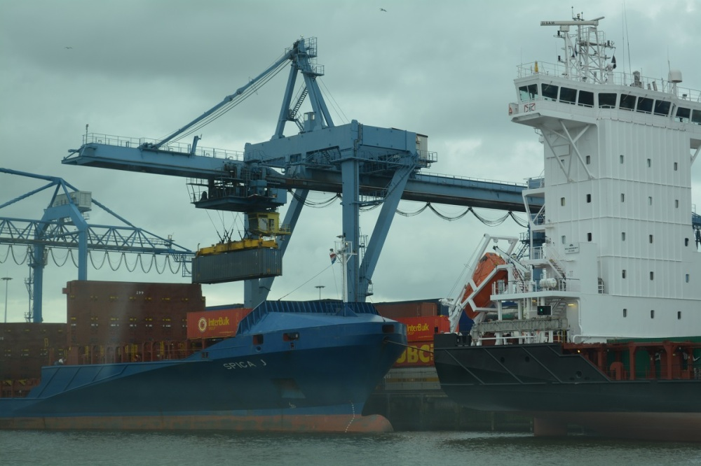 An automatised crane  loads containers onto a ship