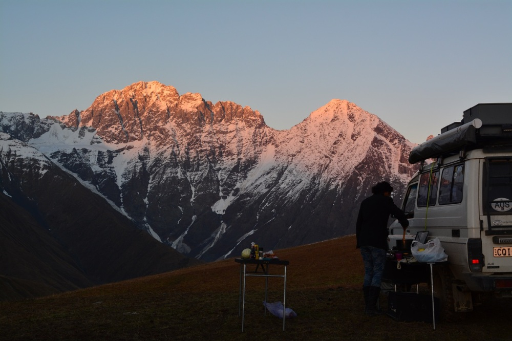 cooking up a feast as the sun descends over the Caucasus mountains.